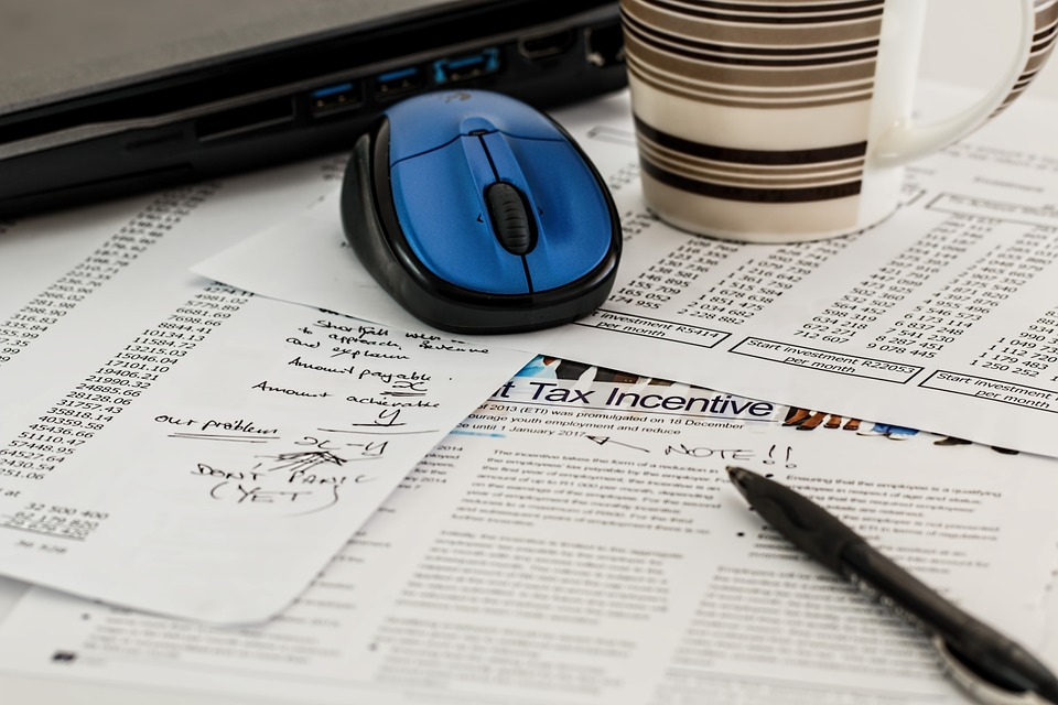Image of laptop, coffee cup, and tax forms and notes